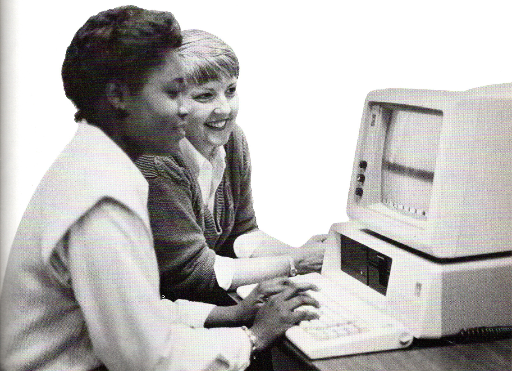 Black and white photo of a white female teacher helping a young black female college student who is sitting at a computer