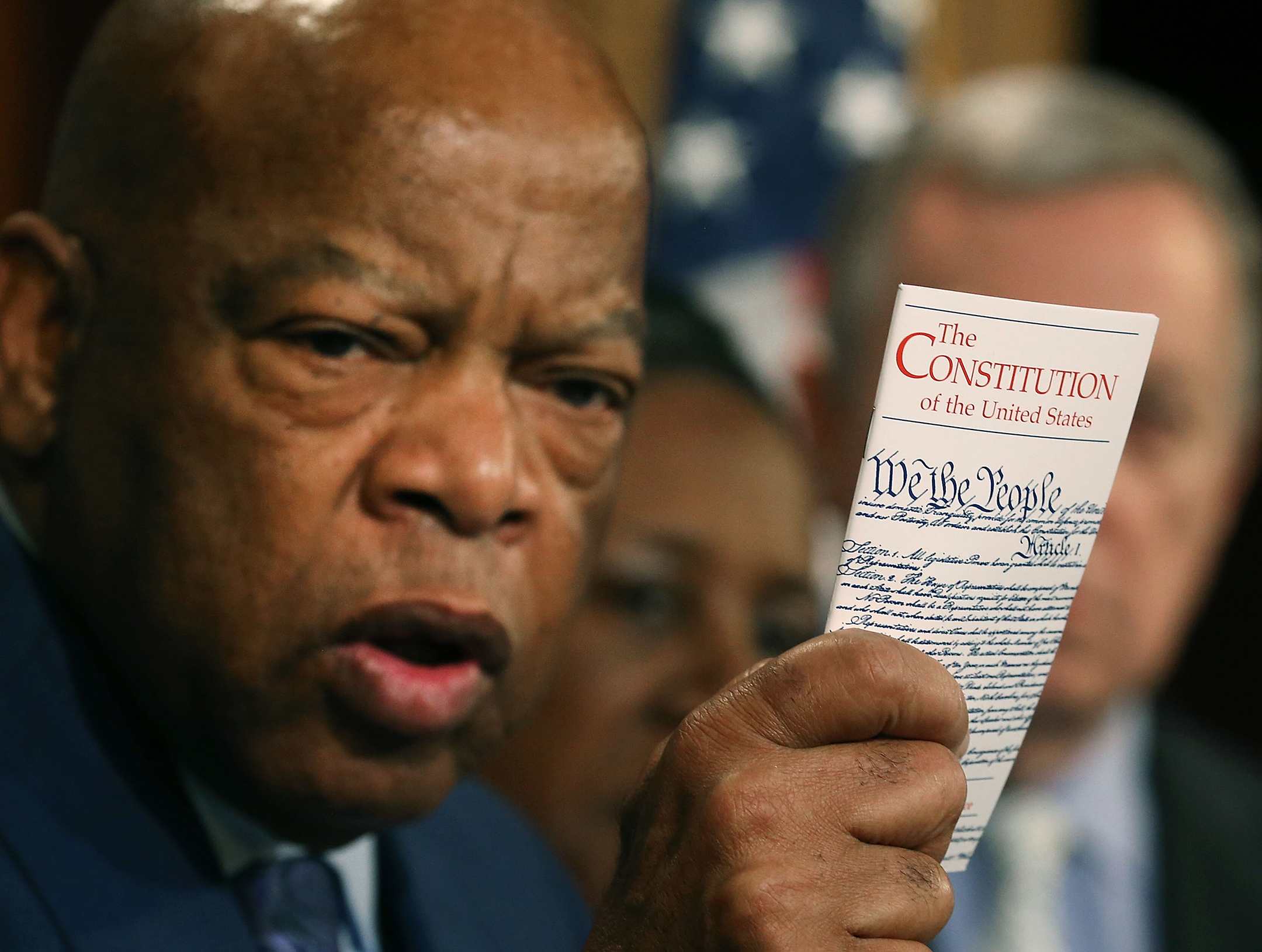 Photograph of John Lewis holding a pocket-sized Constitution, with the Constitution in focus in the foreground