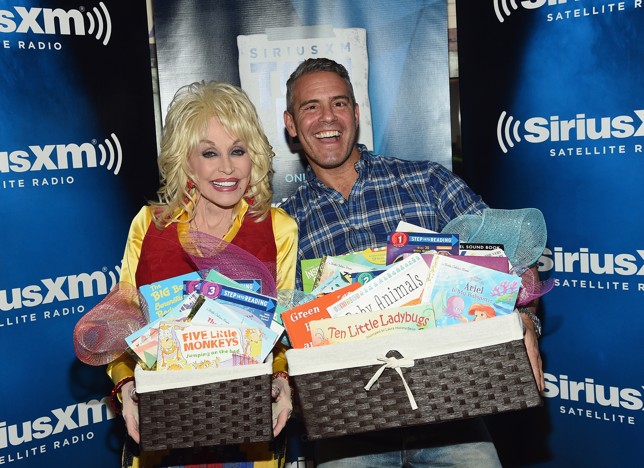 Dolly Parton, on the left, standing next to Andy Cohen, on the right, both smiling wide and holding baskets full of books