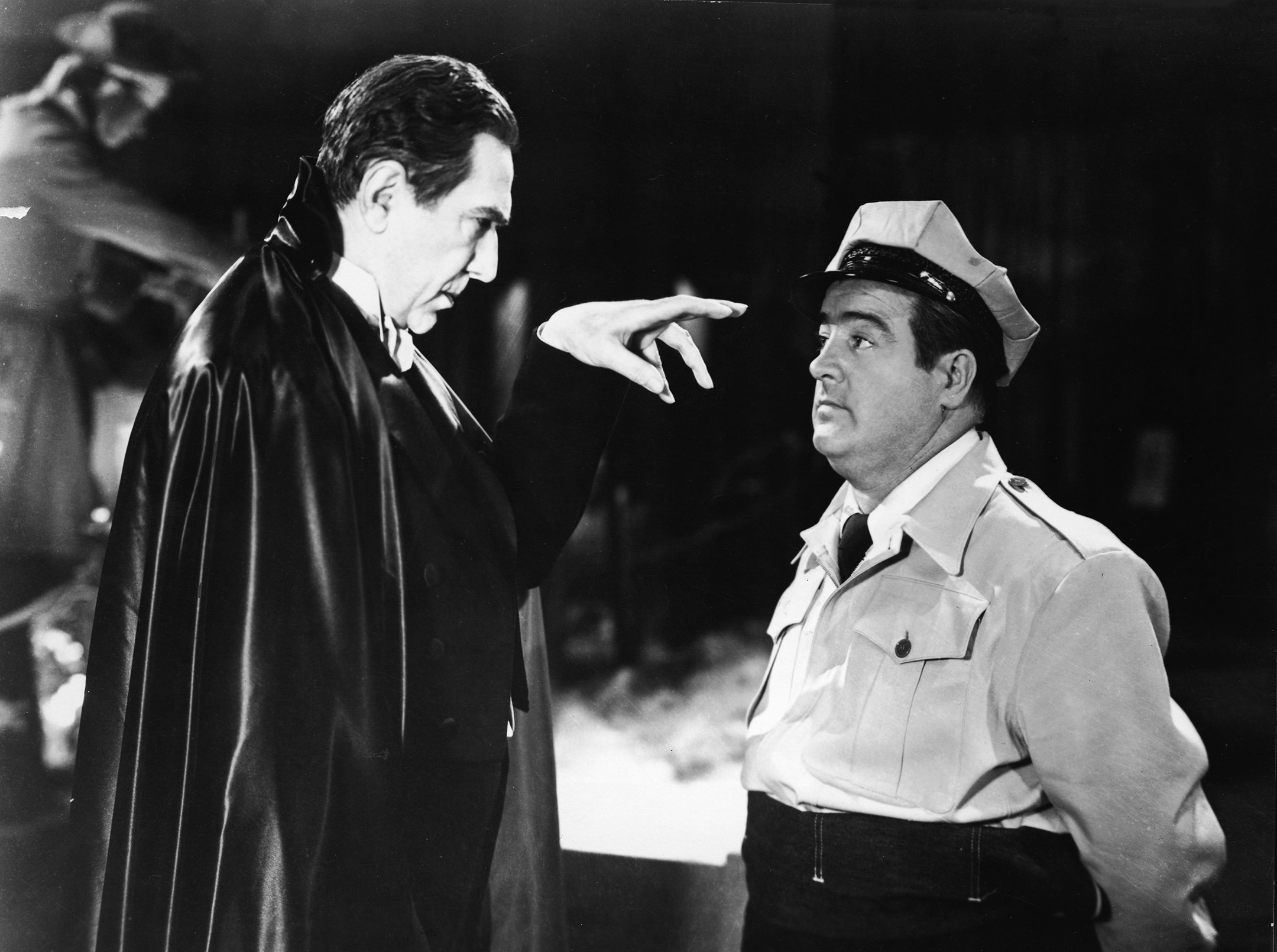 Black and white still from the movie Abbott & Costello Meet Frankenstein showing Dracula staring into the eyes of Lou Costello